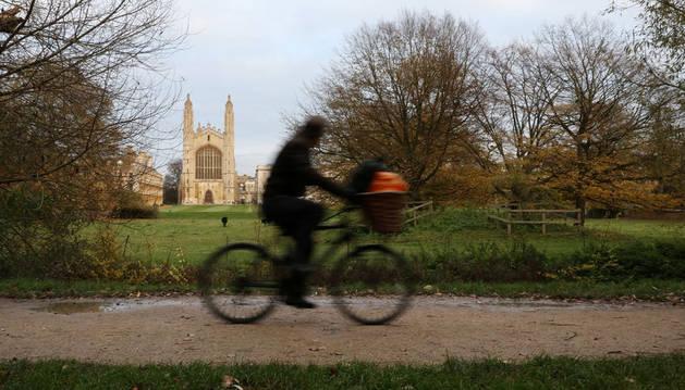 Una bicicleta cruza delante del campus de la Universidad de Cambridge.