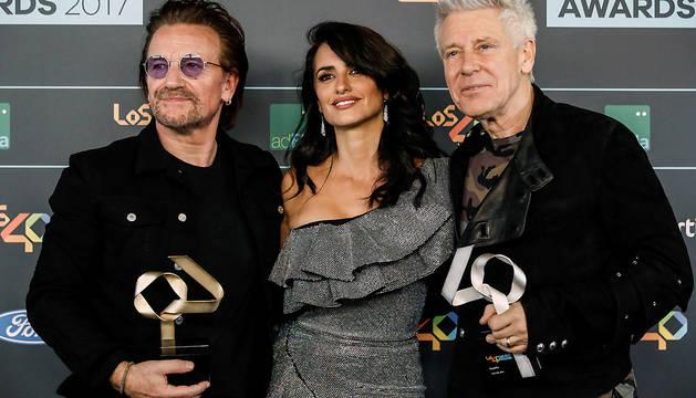 El cantante Bono (i) y el bajista Adam Clayton (d), de la banda irlandesa U2, acompañados por la actriz Penélope Cruz, posan con el Golden Award y con el premio a la Mejor Gira del 2017 para The Joshua Tree Tour 2017.