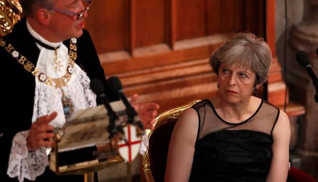La premier británica mira atentamente al alcalde de la City de Londres durante el banquete