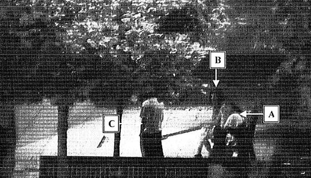 Una de las cámaras próximas al monumento del encierro captó a la denunciante (letra A), sentada en un banco, poco después de los hechos, junto a la pareja que se la encontró llorando y dio aviso a la policía.