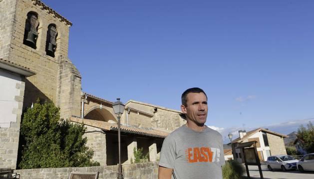 Óscar Zabalza Imízcoz, 38 años, frente a la iglesia de Lizarraga de Izagaondoa, recién restaurada y donde se celebra misa todos los domingos. Al fondo, la antigua escuela, ahora su casa.