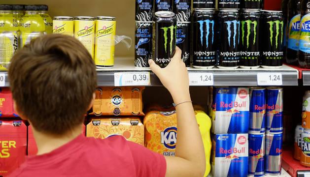 Un menor selecciona una lata de bebida energética en un supermercado.