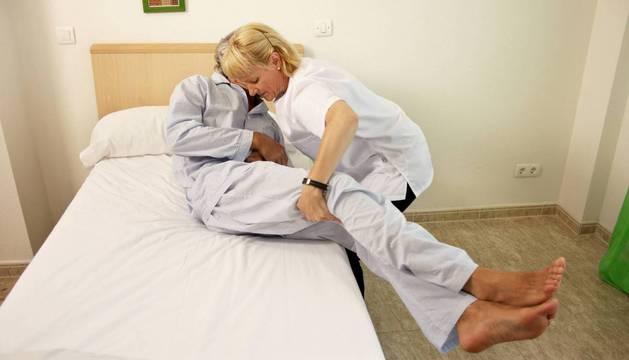 Una mujer ayuda a un anciano a tumbarse en una cama.
