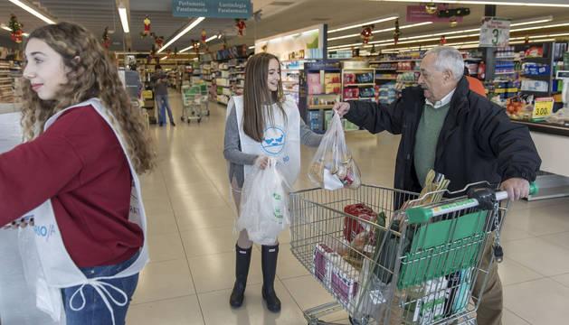 Un hombe cede una bolsa llena de productos a una de las voluntarias del Banco de Alimentos, en un establecimiento de Sarriguren.