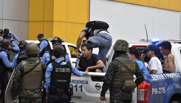 Miembros de la policía detienen a un grupo de ciudadanos presuntamente capturados durante el saqueo de diferentes centros comerciales