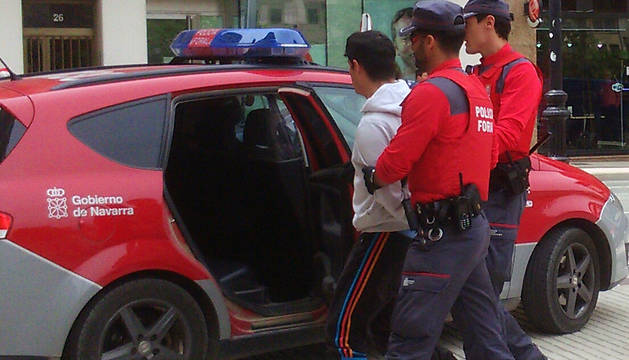 Agentes de la Policía Foral trasladan al vehículo policial a un detenido.