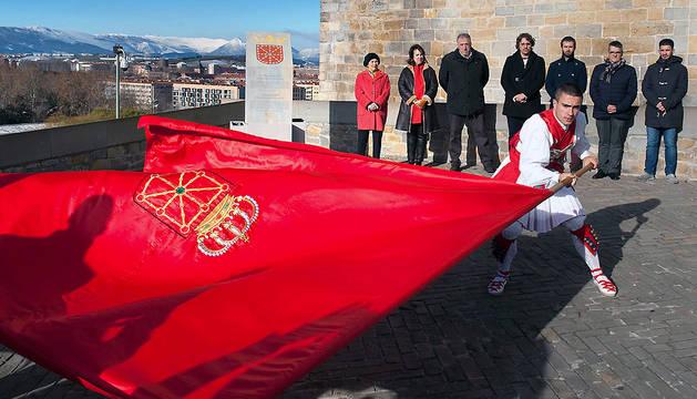 Un dantzari hace ondear la bandera de Navarra.
