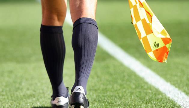 Imagen de las piernas y el banderín de un asistente en un partido de fútbol.