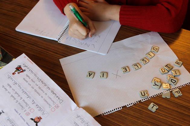 Imagen de un niño escribiendo letras en un cuaderno escolar.