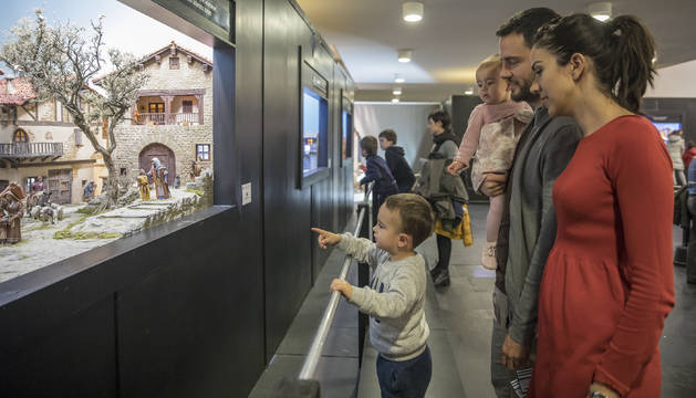 Una familia observa uno de los belenes expuestos en Baluarte.