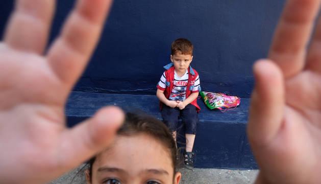 Una niña juega en un campo de refugiados mientras otro niño la observa.