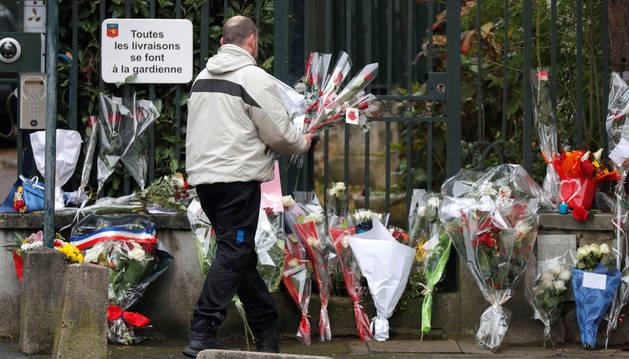 Imagen de un hombre depositando flores en Marnes-la-Coquette, localidad donde murió el cantante Hallyday.
