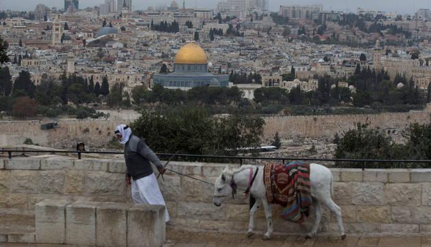 Un palestino tira de su burro mientras camina por el Monte del los Olivos, en Jerusalén.