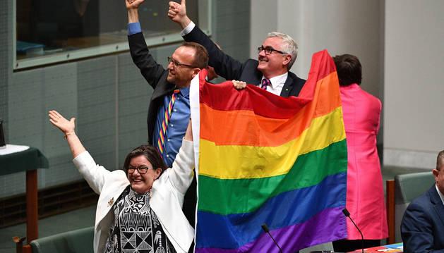 Los diputados Cathy McGowan (i), Adam Brandt (c) y Andrew Wilkie (d) celebran la aprobación del matrimonio entre personas del mismo sexo en el Parlamento en Canberra (Australia)