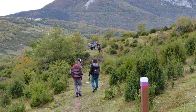 Imagen de varias personas por un trazado de calzada romana recuperado recientemente en el valle de Arce para su disfrute.