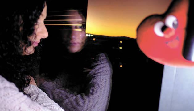 Imagen de Gema Ruiz Rodríguez observando el atardecer por la ventana del salón de su casa en la comarca de Pamplona. Atalaya desde la que ve la vida pasar.