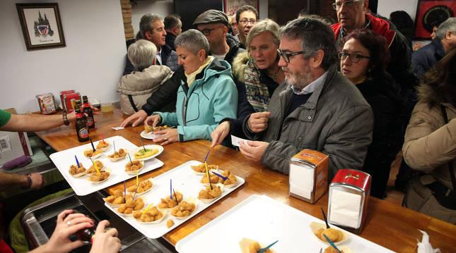 Varias personas esperan su turno para recoger los pinchos de verdura dispuestos en la barra de la peña Athletic de Tudela.