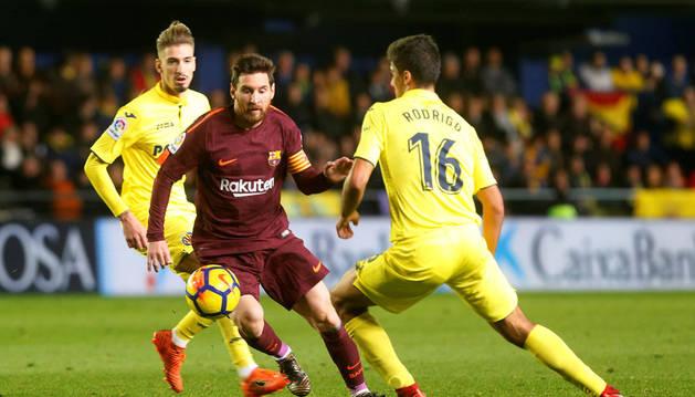 Leo Messi conduce el balón en presencia de dos rivales castellonenses.