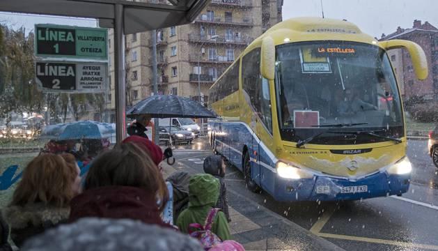 Alumnos esperan el pasado 1 de diciembre el  autobús escolar en el acceso a Estella desde El Volante.