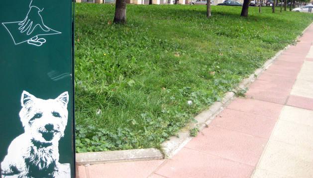 Un cartel, colocado junto a un jardín, recuerda una de las obligaciones a los dueños de los perros.