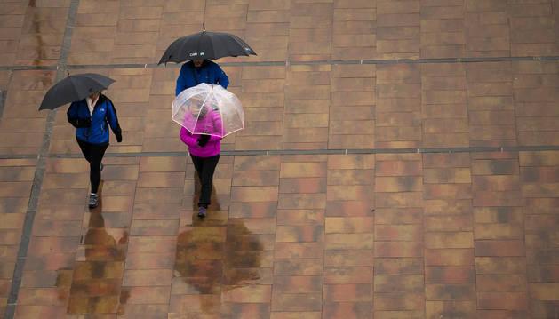 Imagen de tres personas protegiéndose de la lluvia en Pamplona durante el pasado fin de semana.