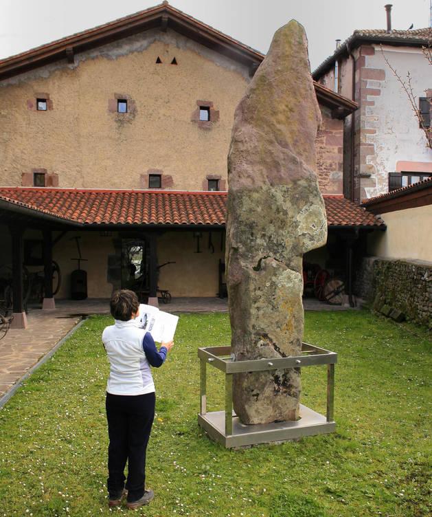 Imagen de una persona contempla el menhir de Soalar, en Elizondo.