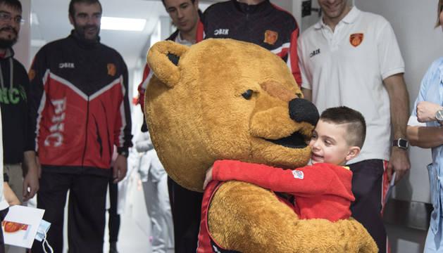 El oso Ronky abraza a uno de los pacientes en presencia de jugadores y el técnico del Basket Navarra.