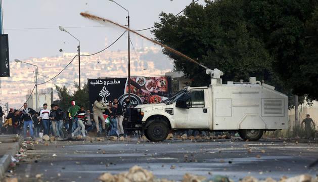 Palestinos lanzan piedras a un cañón de agua del Ejército israelí durante los enfrentamientos entre manifestantes palestinos y soldados israelíes en el puesto de control de Huwwara, cerca de la ciudad palestina de Nablus (Palestina).