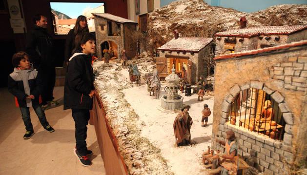 Dos niños, acompañados por sus padres, contemplan uno de los dos belenes tradicionales de la exposición.