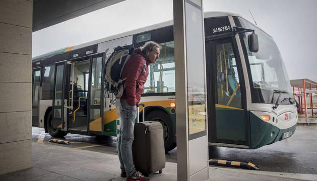 Un viajero consulta el cartel informativo del transporte urbano comarcal, anteayer, en el aeropuerto de Noáin.