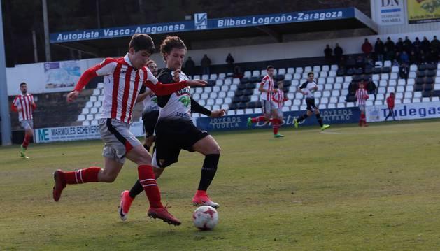 El jugador del Athletic, Jesús Areso, conduce el balón ante la presión del defensa del Tudelano, Álvaro Meseguer.