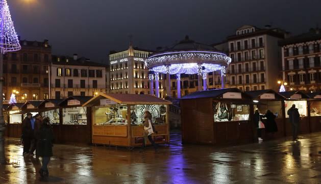 Vista nocturna de la Plaza del Castillo, iluminada por la llegada de la Navidad y la instalación de la tradicional feria que copará el espacio durante estos días.