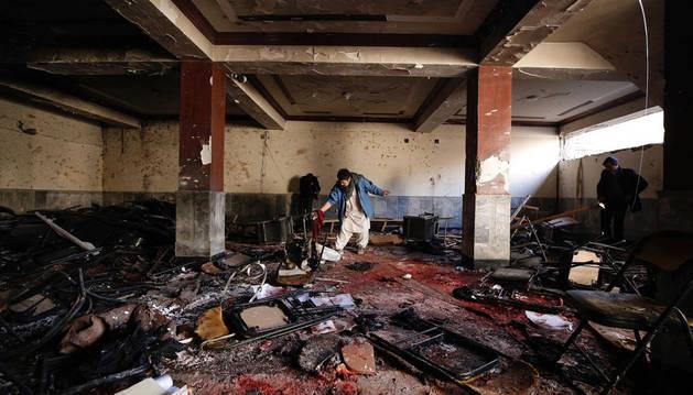 En la imagen, un afgano comprueba los destrozos en el escenario del ataque suicida en Kabul, capital de Afganistán.
