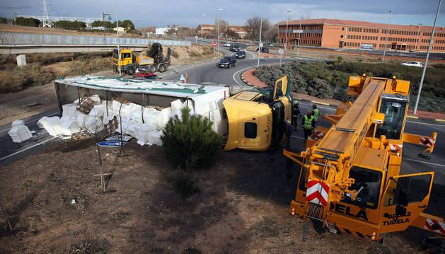 El camión volcado este viernes en la rotonda de la N-121-C ubicada junto al Instituto de Educación Secundaria Valle del Ebro de Tudela -al fondo de la imagen-.