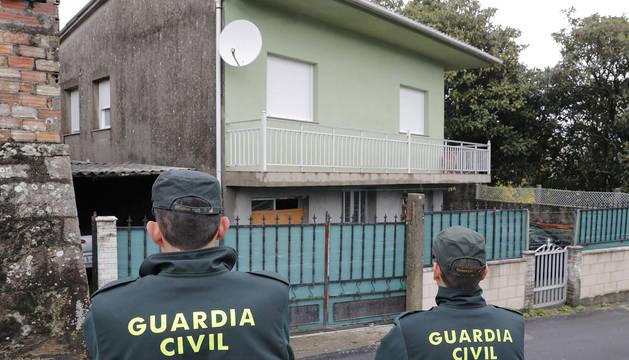 Dos guardias civiles, junto a la casa del detenido en Rianxo.