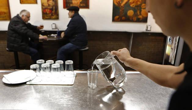 Un camarero sirve agua del grifo en el bar Itziar de Pamplona, uno de los establecimientos que  lo hace desde hace años.
