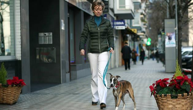 Maite Baraibar Castillo paseando con su galgo River por una calle del barrio de Iturrama de Pamplona.
