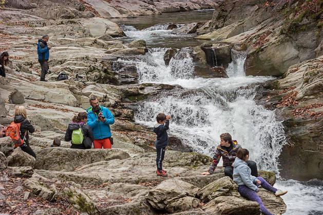 Imagen de un grupo de turistas descansando en la Cascada del Cubo, en la Selva de Irati.