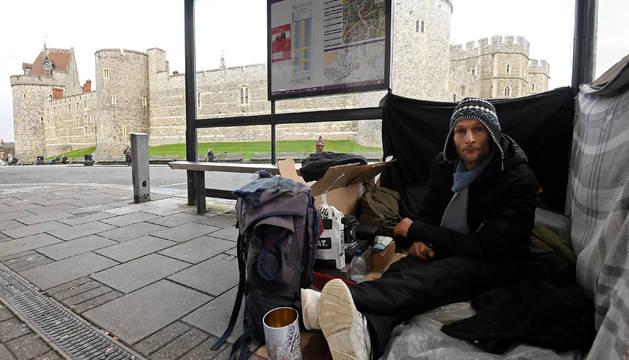 Stuart, un vagabundo que emplea como refugio una parada de autobús, frente al castillo en el que tendrá lugar la boda