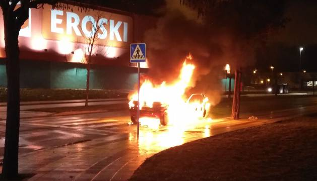 El coche envuelto en llamas.