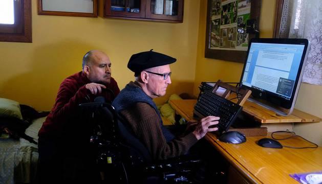 """Delante del ordenador, Tomás Belzunegui junto a su cuidador y """"gran amigo"""", Elard Vargas Álvarez."""