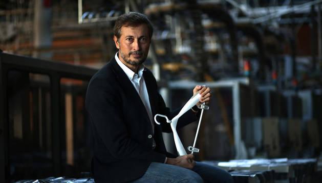 Imagen de Jesús Aranda, fundador y director de DataJuicers, en la rotativa de Diario de Navarra, con una percha como símbolo de la aplicación de la tecnología a la moda.