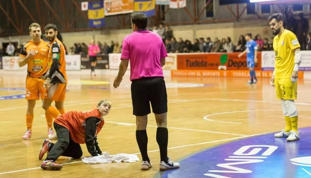 El 'mopero' del Aspil se afana por secar el suelo entre los jugadores de ambos equipos y el árbitro del encuentro.