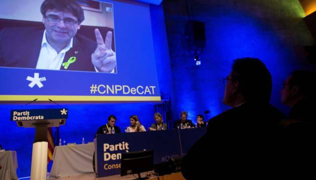 El expresidente del PDeCAT, Artur Mas (d) , observa la intervención por videoconferencia de Carles Puigdemont (c), durante el consell nacional del partido en plena polémica por su investidura a distancia