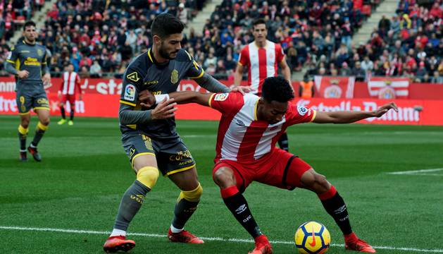 El defensa colombiano del Girona Johan Mojica protege el balón ante el centrocampista de la UD Las Palmas Hernán Toledo.