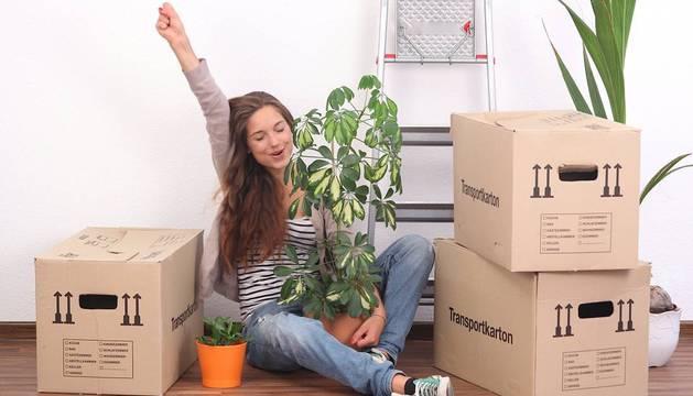 Una chica en plena mudanza, rodeada de cajas llenas de enseres.