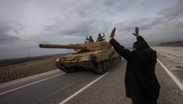 Un hombre celebra el paso de un tanque con soldados turcos cerca de la frontera turco-siria