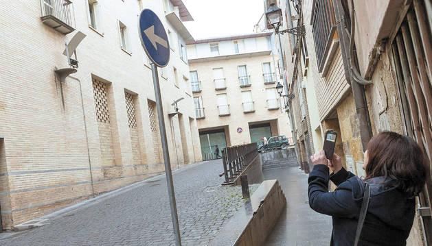 Una mujer hace una foto con su teléfono a la señal puesta al revés.