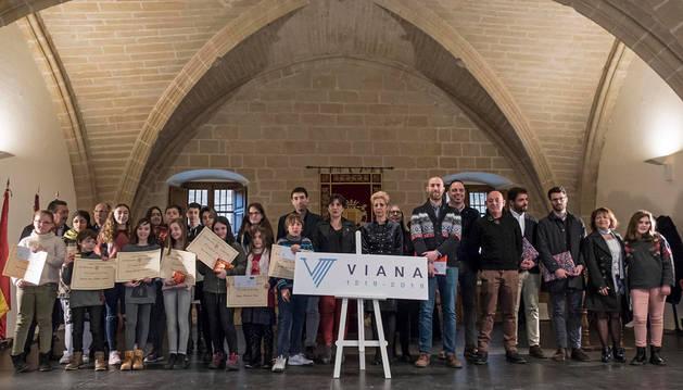 Imagen de la consejera y la alcaldesa de Viana (detrás del logotipo que será la imagen del VIII centenario) con su autor (a su izda.), homenajeados y escolares premiados en la casa de cultura.