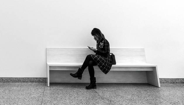 Imagen de una mujer consultando su teléfono móvil sola en un banco.